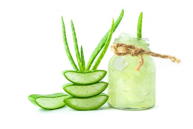 Aloe fresca vera con la fetta nell'isolato di vetro su bianco