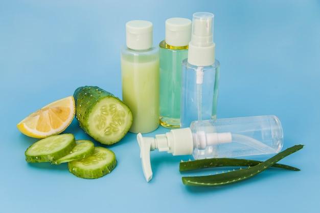 Aloe vera fresca; bottiglie di spruzzo di fette di limone e cetriolo su sfondo blu