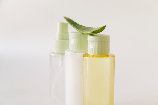 Aloe vera sopra le bottiglie spray su sfondo bianco