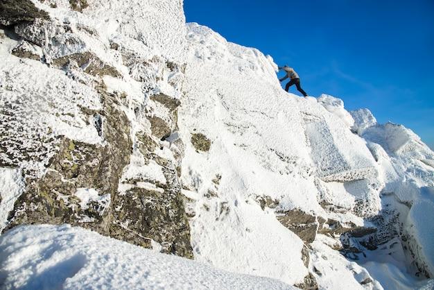 Alpinista arrampicata sulla cima della montagna ricoperta di ghiaccio e neve, uomo escursionista andando in cima alla roccia.