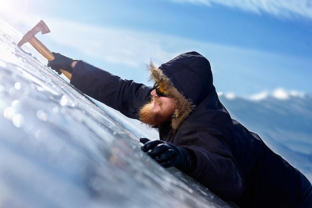 Alpinista barbuto di redhead in occhiali gialli protettivi con piccozza che si blocca su roccia ghiacciata
