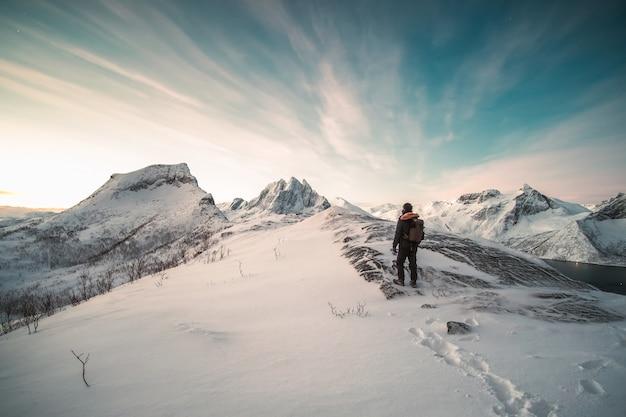 Alpinista in piedi sulla cima della montagna innevata