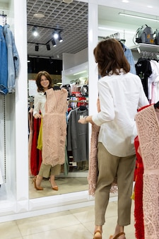 Alta bella giovane donna in camicia bianca si trova davanti allo specchio nel negozio di abbigliamento cercando elegante abito da sera beige