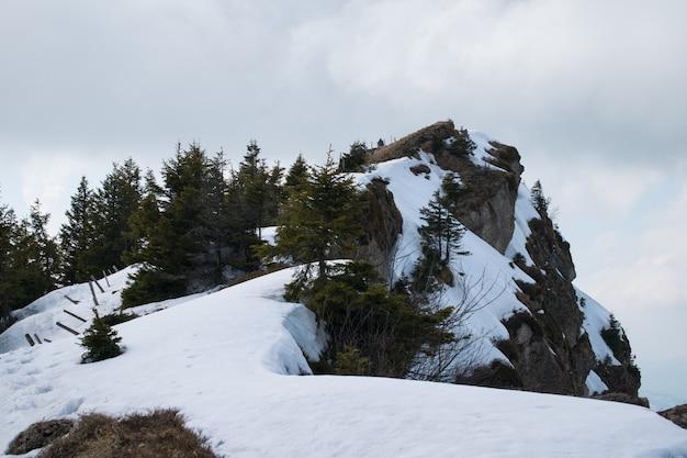 Alta scogliera rocciosa ricoperta di neve sotto un cielo nuvoloso