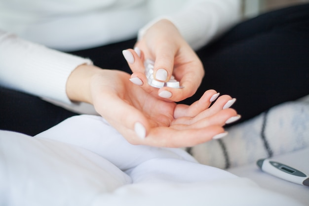 Alta temperatura. chiuda sulla stretta malata della donna nella sua pillola della mano