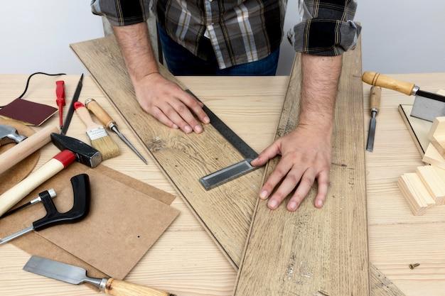 Alta vista che tiene il concetto di officina di falegnameria di tavole di legno