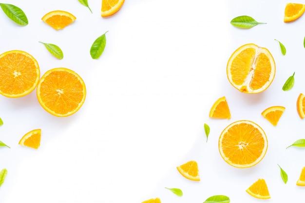 Alta vitamina c, succosa e dolce. frutta arancio fresca con le foglie verdi su fondo bianco