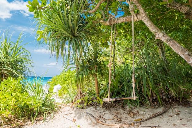 Altalena con albero blu cielo e nuvole sullo sfondo, mare blu e spiaggia di sabbia bianca sull'isola similan,
