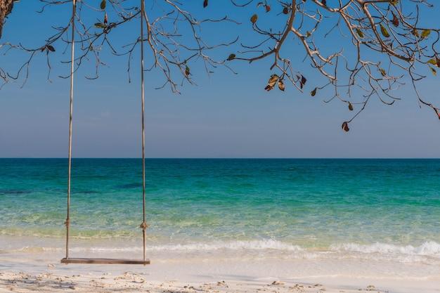 Altalena in legno sulla spiaggia con albero