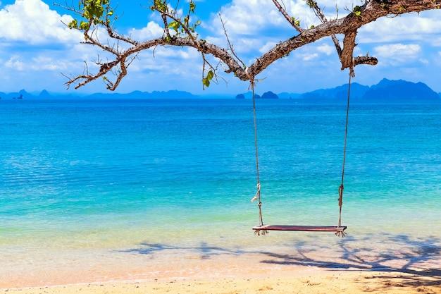 Altalena in legno sulla spiaggia tropicale con acqua limpida e cielo blu, un paradiso per le vacanze