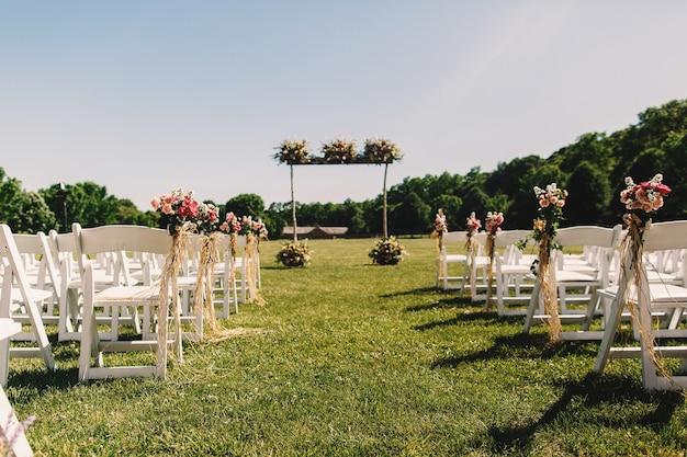 Altare nuziale fatto di bastoni di legno e stand di mazzi di fiori