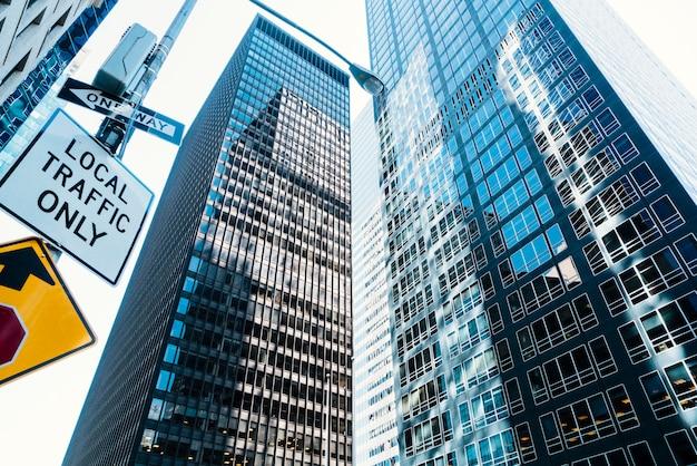 Alti grattacieli di vetro e segnale stradale sulla strada