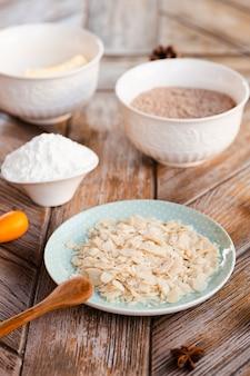 Alto angolo degli ingredienti della torta con il cucchiaio di legno