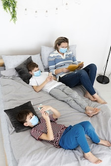 Alto angolo dei bambini a letto con le maschere mediche e la madre che leggono un libro