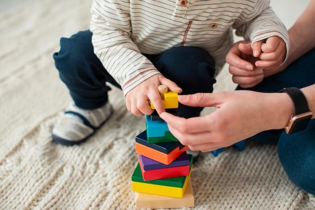 Alto angolo del bambino che gioca a casa con la madre