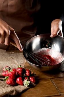 Alto angolo del cuoco unico che sbatte le fragole in ciotola con zucchero