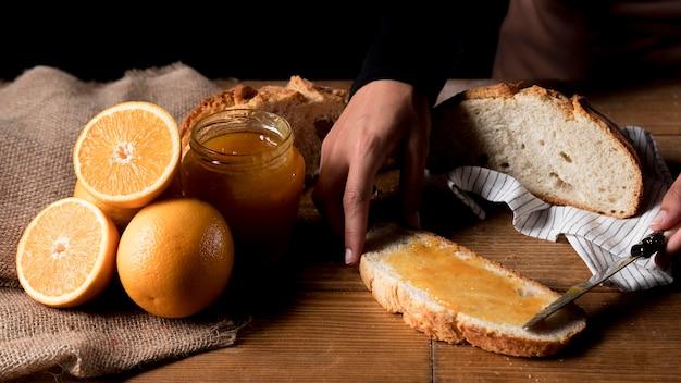 Alto angolo del cuoco unico che spande la marmellata di arance su pane