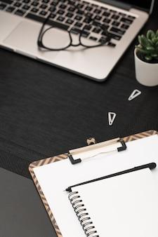 Alto angolo del desktop con il taccuino sopra il blocco note e il computer portatile