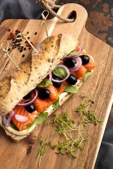 Alto angolo del panino al salmone con olive e cipolle