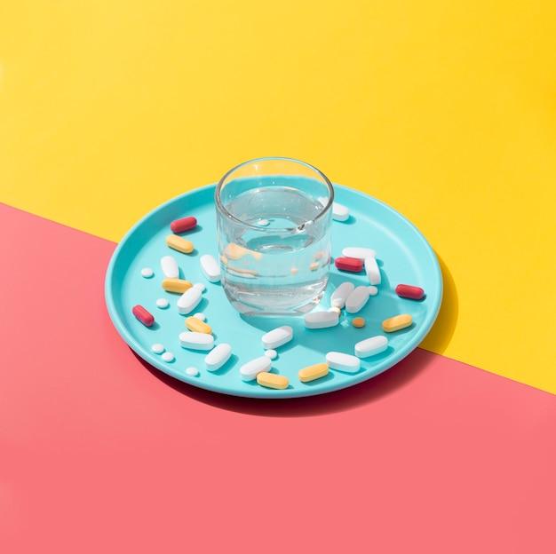 Alto angolo del vassoio con le pillole e il bicchiere d'acqua