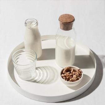 Alto angolo della bottiglia per il latte con le noci sul vassoio
