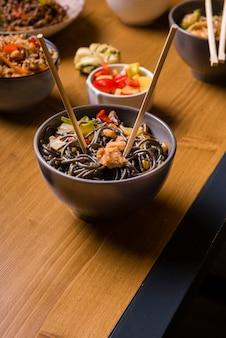 Alto angolo della ciotola di tagliatelle con l'altro alimento asiatico