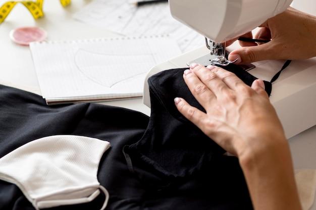 Alto angolo della donna che cuce la maschera di protezione dal tessuto