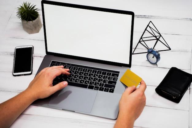Alto angolo della mano sulla parola chiave del computer portatile sulla tavola di legno