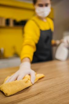Alto angolo della superficie di pulizia defocused barista mentre indossa maschera medica
