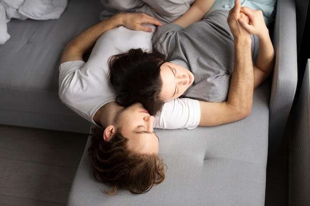 Alto angolo delle coppie che dormono sul sofà