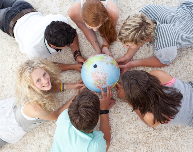 Alto angolo di adolescenti sul pavimento esaminando un mondo terrestre