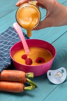 Alto angolo di alimenti per l'infanzia versati nella ciotola con carote e ciuccio