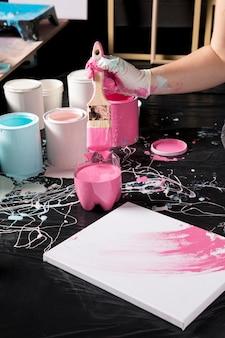 Alto angolo di artista con vernice rosa su tela