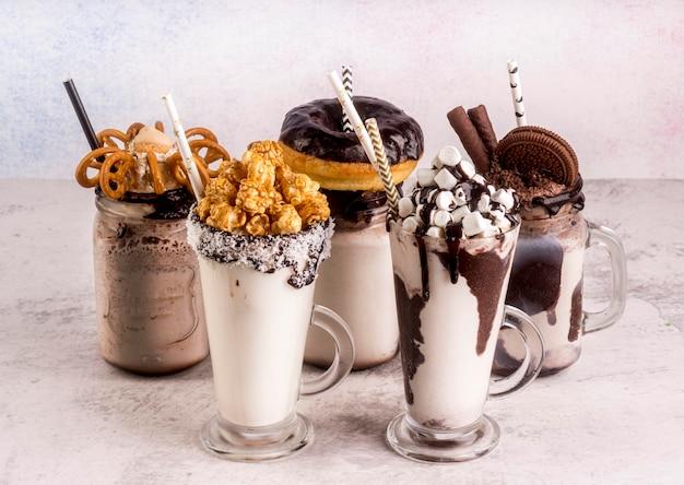 Alto angolo di assortimento di dessert con cannucce e cioccolato