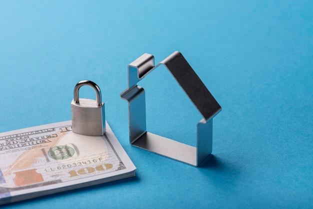 Alto angolo di banconote con serratura e casa