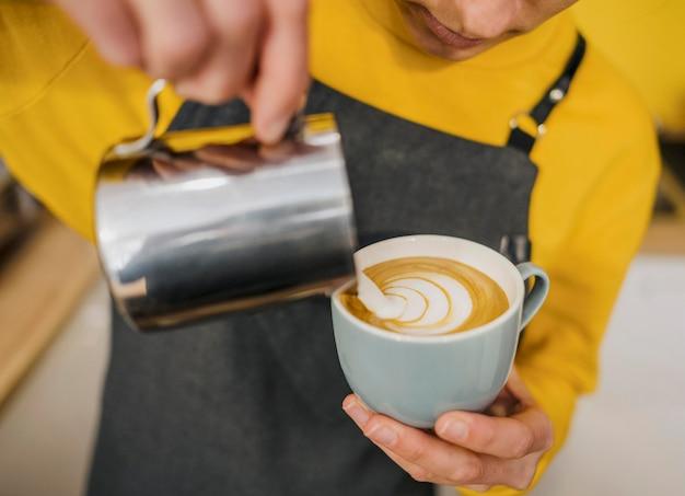 Alto angolo di barista che decora la tazza di caffè con latte