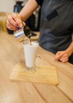 Alto angolo di barista che fa la bevanda del caffè