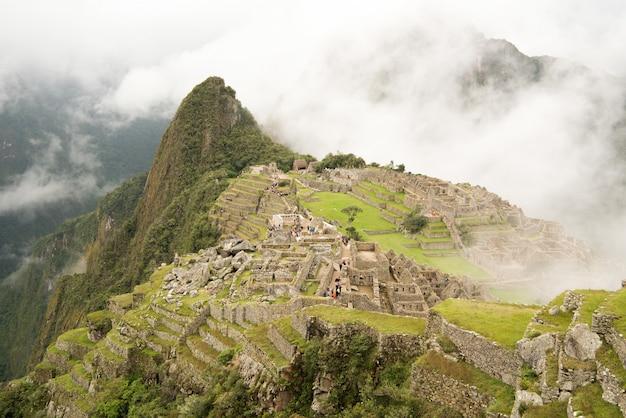 Alto angolo di bella cittadella di machu picchu circondato da montagne nebbiose a urubamba, perù
