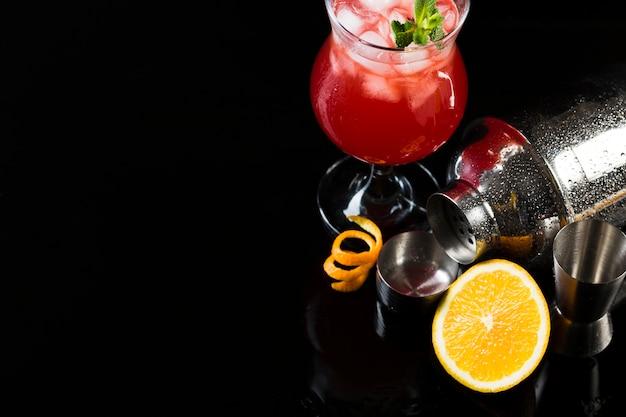 Alto angolo di bicchiere da cocktail con shaker e arancia