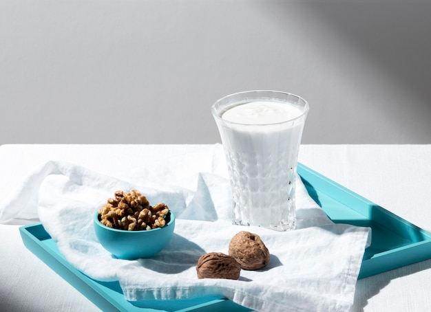 Alto angolo di bicchiere di latte intero con noci