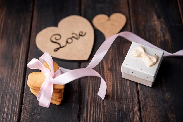 Alto angolo di biscotti a forma di cuore con presente e nastro