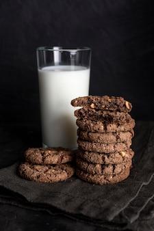 Alto angolo di biscotti al cioccolato con un bicchiere di latte