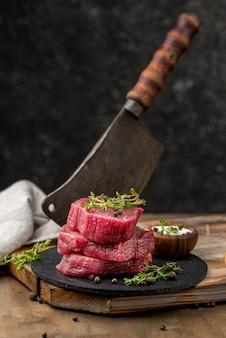 Alto angolo di carne su ardesia con erbe e mannaia