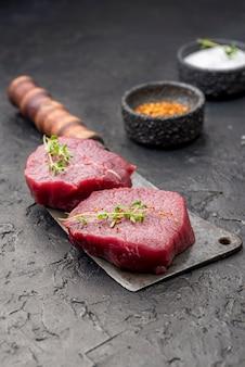 Alto angolo di carne su mannaia con spezie