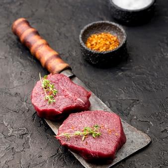 Alto angolo di carne sulla mannaia con spezie ed erbe