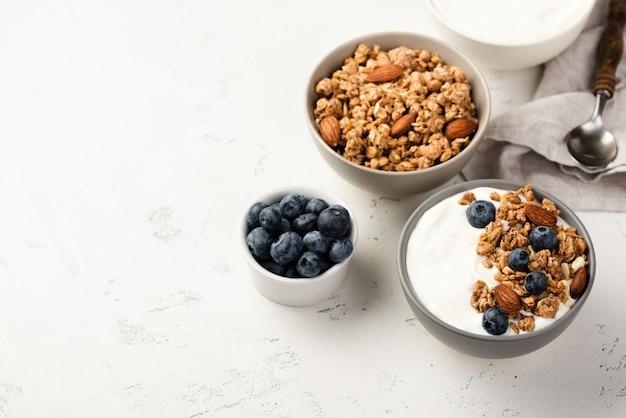 Alto angolo di ciotole con cereali per la colazione e mirtilli