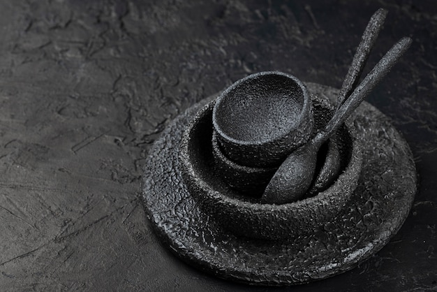 Alto angolo di ciotole nere e cucchiai su ardesia