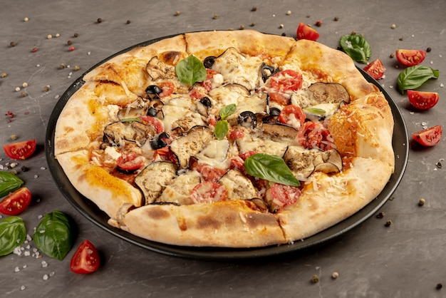 Alto angolo di deliziosa pizza con pomodori e basilico