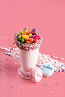 Alto angolo di dessert con caramelle colorate e cannucce