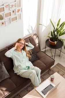 Alto angolo di donna che lavora a casa in pigiama